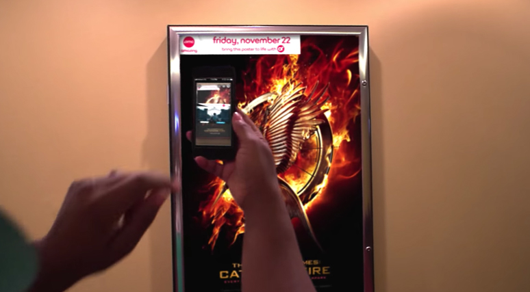 Social media trends in 2017 augmented reality AMC theatre chain app in action over a Hunger Games movie poster
